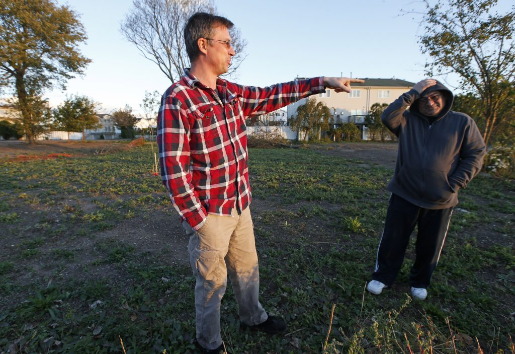 Friends and former neighbors Oleg Elperin (L) and Zachary Rosenfeld stand in a vacant lot in their former neighborhood in Oakwood Beach, Staten Island, which was ravaged in Superstorm Sandy. Both men used to live in the building behind them but relocated to higher ground blocks away in New Dorp. (AP Photo/Kathy Willens)