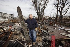 Dean Rasinya poses with a street sign for Irving Walk salvaged from the wreckage of a fire that ravaged Breezy Point during Superstorm Sandy. (AP Photo/Mark Lennihan, File)