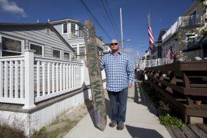 Kieran Burke posing last week with an Irving Walk sign salvaged from the debris fire that swept through Breezy Point during Superstorm Sandy. A single story-home, left, that survived the fire, is now surrounded by new two-story homes mounted on tall concrete foundations. (AP Photo/Mark Lennihan)