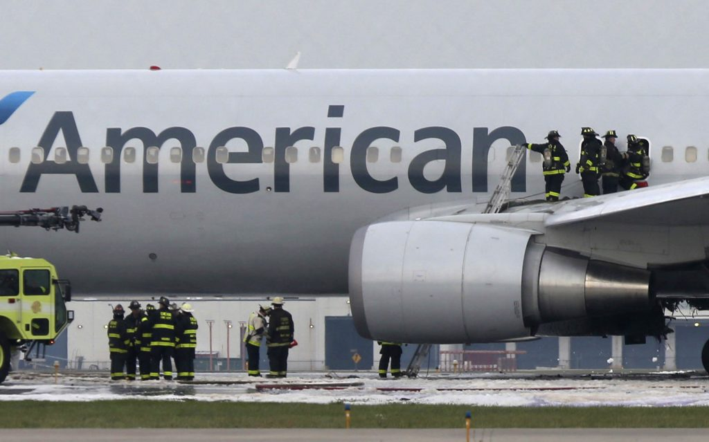 Chicago firefighters at the fire-damaged American Airlines jet at O'Hare Airport on Friday. (Antonio Perez/ Chicago Tribune/Chicago Tribune via AP)