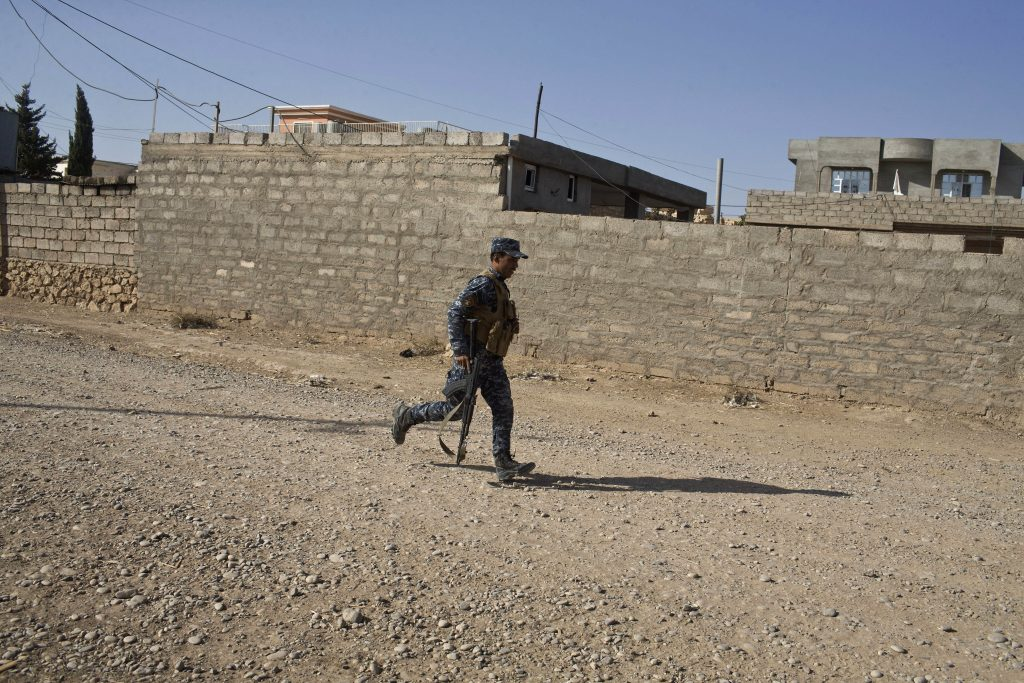 An Iraqi Federal Police officer runs for cover in the town of Shura, some 30 kilometers south of Mosul, Iraq, Saturday, Oct. 29, 2016. Iraqi troops approaching Mosul from the south advanced into Shura on Saturday after a wave of US led airstrikes and artillery shelling against Islamic State positions inside town. (AP Photo/Marko Drobnjakovic)