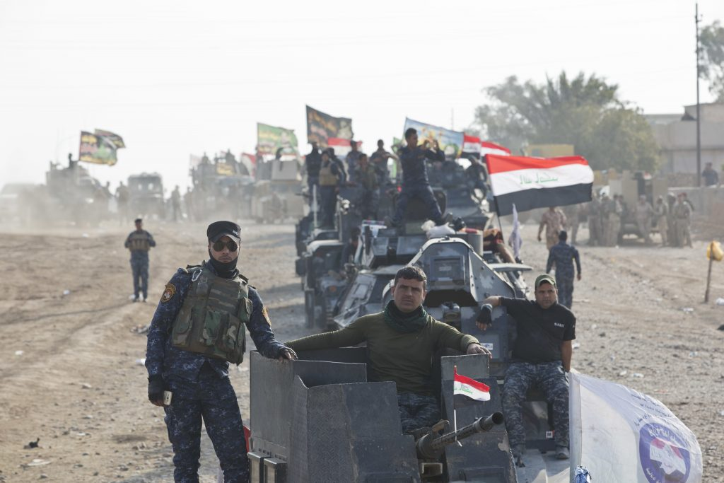 Iraqi Federal Police officers observe as air and ground strikes hit the town of Shura, some 30 kilometers south of Mosul, Iraq, Saturday, Oct. 29, 2016. Iraqi troops approaching Mosul from the south advanced into Shura on Saturday after a wave of US led airstrikes and artillery shelling against Islamic State positions inside town. (AP Photo/Marko Drobnjakovic)