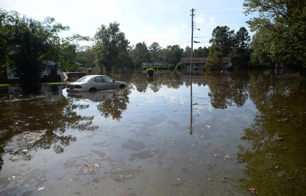 A car in a yard along Cedar Lane, is partially submerged in floodwaters from the rain of Hurricane Matthew, Friday, Oct. 14, 2016, in Kinston, N.C. (Zach Frailey/Daily Free Press via AP)
