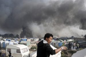 "Smoke billows from burning shelters in ""the jungle."" (AP Photo/Thibault Camus)"
