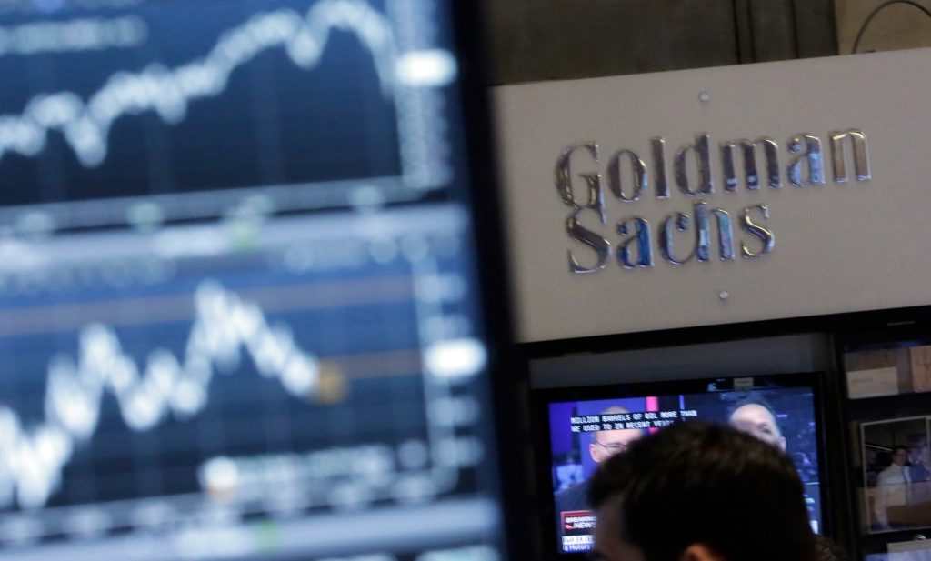 FILE - A trading post on the floor of the New York Stock Exchange is juxtaposed with the Goldman Sachs booth. (AP Photo/Richard Drew, File)