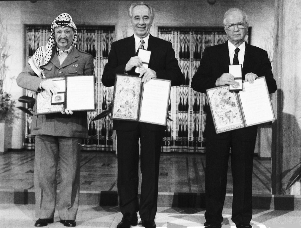 (L-R) PLO leader Yasser Arafat, Israeli Foreign Minister Shimon Peres and Israeli Prime Minister Yitzhak Rabin pose with their medals and diplomas, after receiving the 1994 Nobel Peace Prize in Oslo's City Hall, on Dec. 10, 1994. (AP Photo, File)