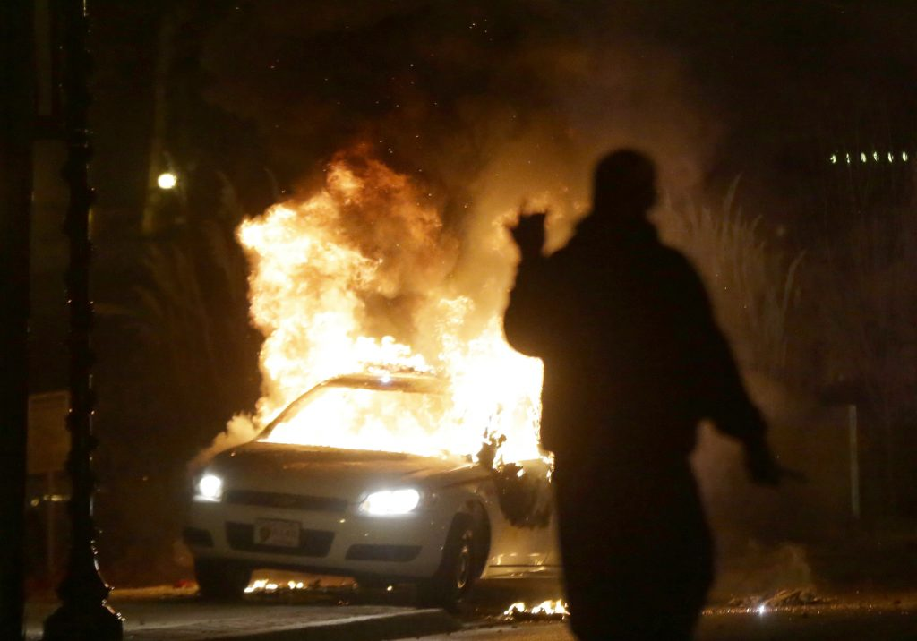 A police car is set on fire during protests after the announcement of the grand-jury decision in the shooting of Michael Brown in Ferguson, Mo., on Nov. 24, 2014. (AP Photo/Charlie Riedel, File)
