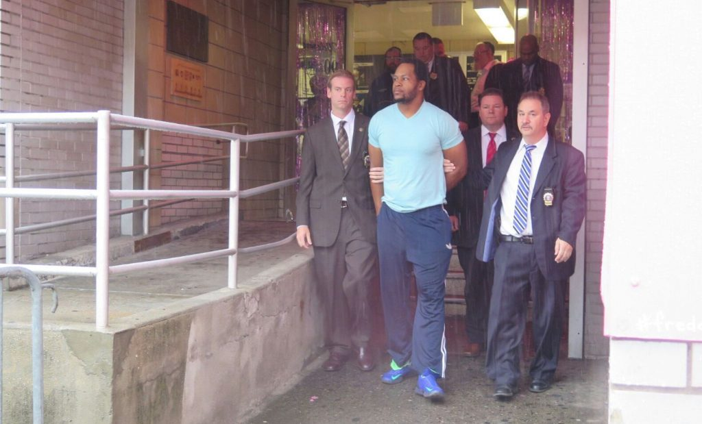 Erskine Felix being led out of the 90th Precinct stationhouse Friday morning. (ABB)