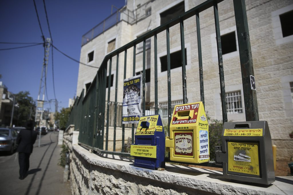 Community charity boxes hang on a fence in a street in the Ultra Orthodox neighborhood of Sanhedria in Jerusalem, September 22, 2014. Photo by Nati Shohat/Flash90 *** Local Caption *** çøãé ÷åôñàåú öã÷ä öã÷ä ÷åôñà ÷åôñä øçåá ñðäãøéä éøåùìéí