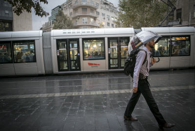 A man holds an umbrella to protect himself from the rain in downtown Jerusalem on October 27, 2015, during the first rain of the upcoming winter. Photo by Yonatan Sindel/Flash90