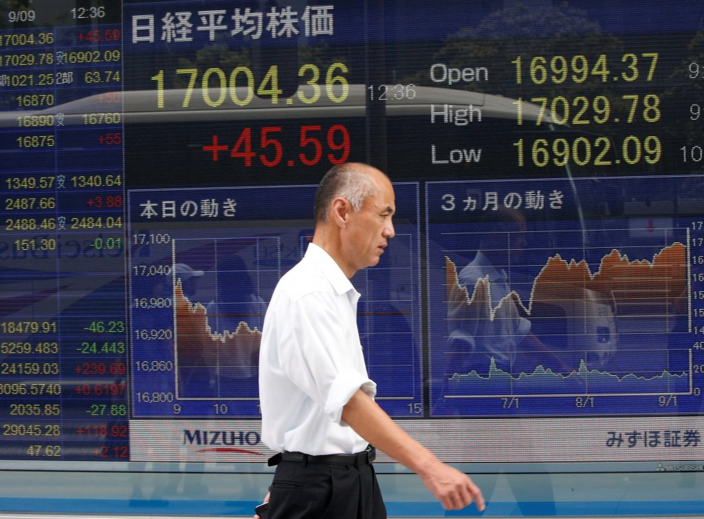 A man walks past a stock quotation board outside a brokerage in Tokyo, Japan, September 9, 2016. REUTERS/Kim Kyung-Hoon