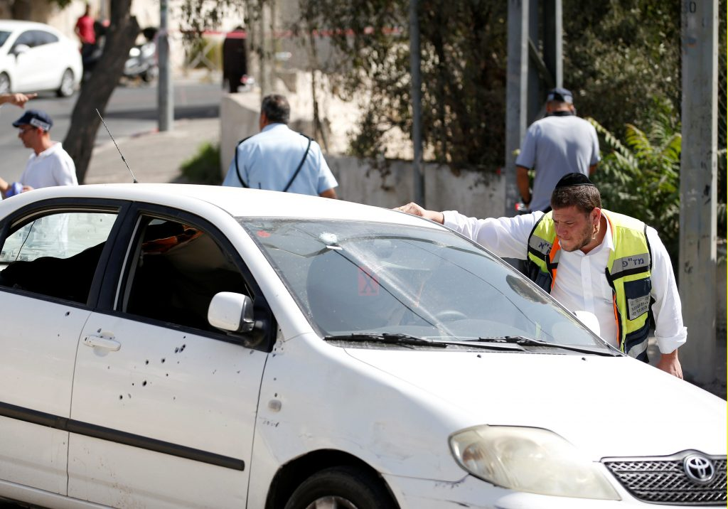 An Israeli emergency worker looks into a car covered with bullet holes after Israeli police killed an Arab assailant who fired from the car wounding several people in Jerusalem, in what an Israeli police spokesperson described as a terrorist attack, in Sheikh Jarrah in East Jerusalem October 9, 2016. REUTERS/Ronen Zvulun