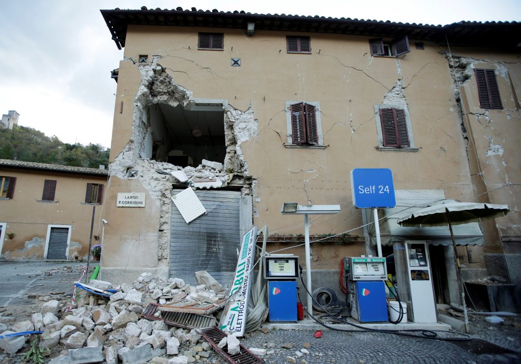 A collapsed building is seen next to a petrol station after an earthquake in Visso, central Italy, October 27, 2016. REUTERS/Max Rossi