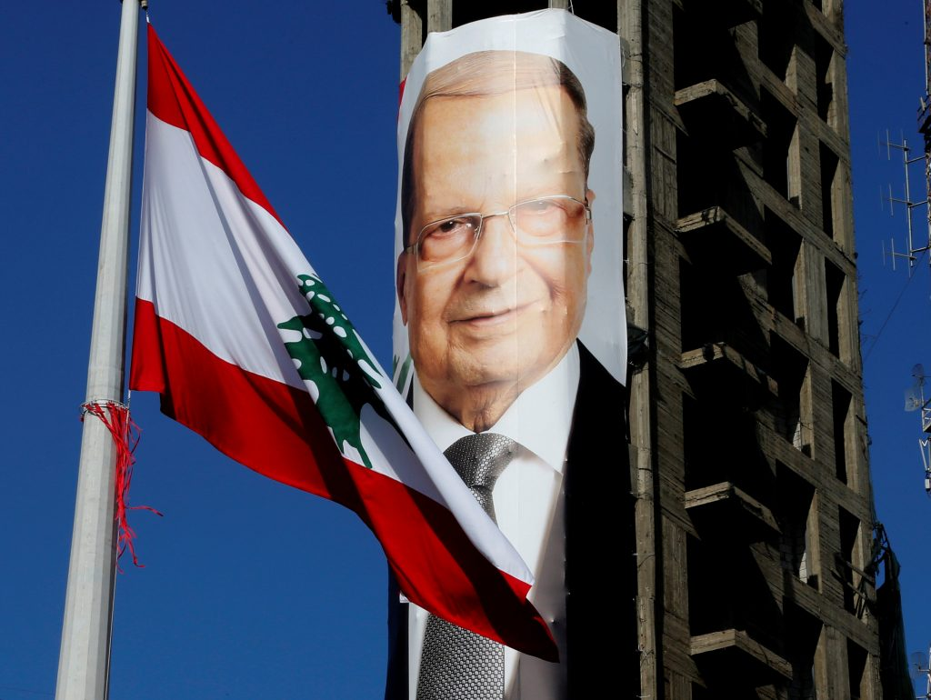 A Lebanese flag flutters near a picture of Christian politician and FPM founder Michel Aoun on a building prior to presidential elections in Beirut, Lebanon October 30, 2016. REUTERS/Mohamed Azakir