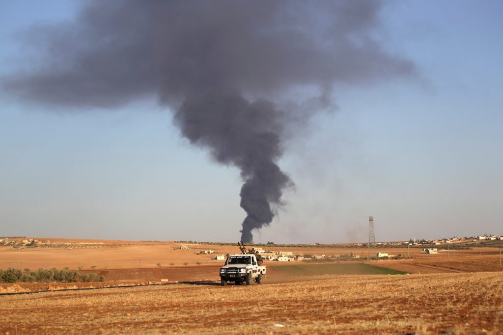 Rebel fighters ride a military vehicle near rising smoke from al-Bab city, northern Aleppo province, Syria October 26, 2016. REUTERS/Khalil Ashawi