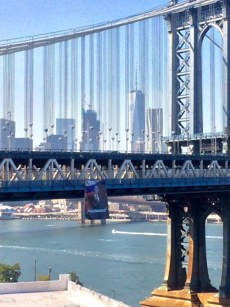 "A giant banner with an image of Russian President Vladimir Putin and the word ""peacemaker"" hangs Thursday on the Manhattan Bridge."
