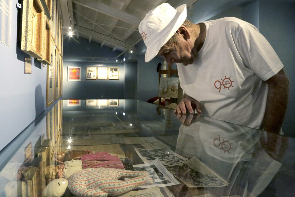 In this Thursday, Sept. 8, 2016 photo, Murray Greenfield, 90, looks around an exhibition about interned Jews at the Center of Visual Arts and Research in Nicosia, Cyprus. He's wearing a custom-made T-shirt presented to him by his family with the number 90, for his 90th birthday. (AP Photo/Petros Karadjias)