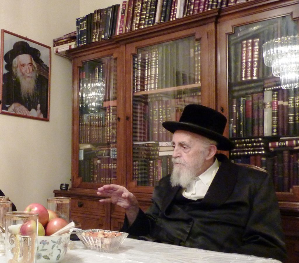 """Harav Williger, zt""""l. Note the photo of his Rebbe, zy""""a, on the wall of the dining room."""