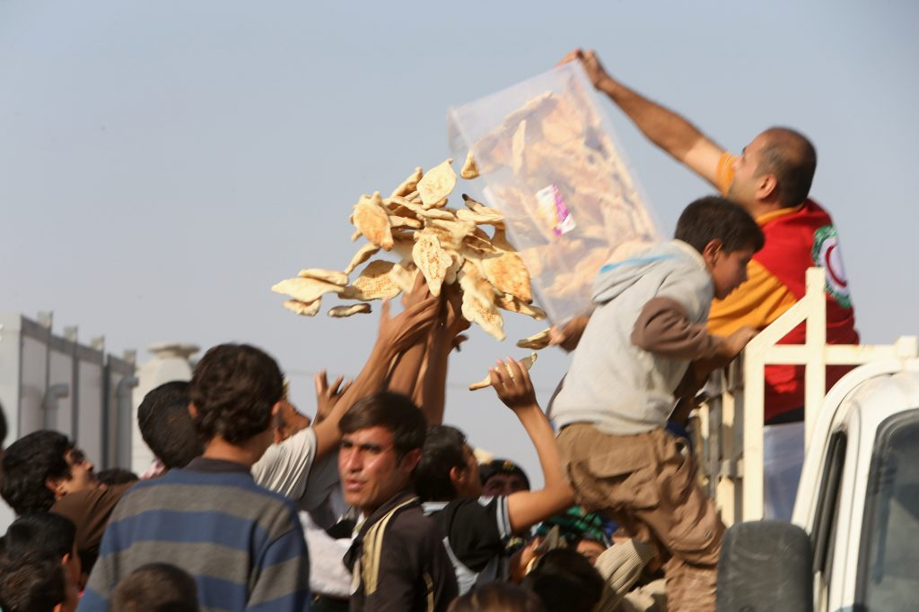 Displaced people, who fled from Mosul due to Islamic State violence, receive food in Khazer refugee camp, east of Mosul, Iraq, on Monday. (Reuters/Alaa Al-Marjani)