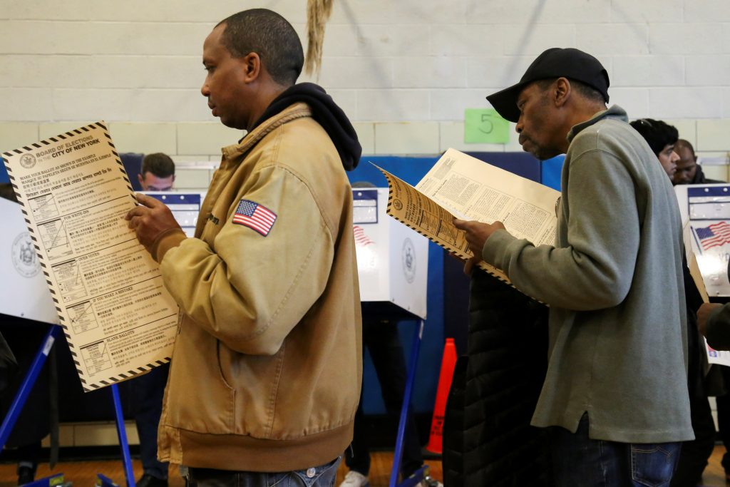 Men read their ballots before voting at a polling station in the Harlem neighborhood of Manhattan. (Reuters/Bria Webb)