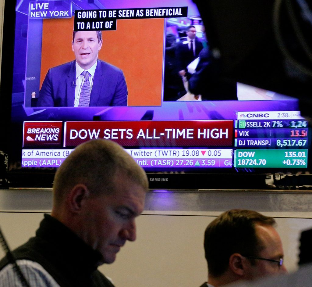 """Traders work on the floor of the New York Stock Exchange on Thursday, as a TV screen shows the headline """"Dow Sets All-Time High."""" (Reuters/Brendan McDermid)"""