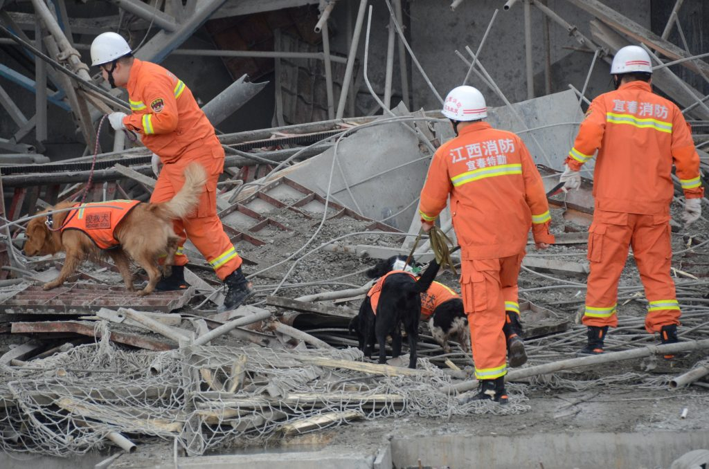 Rescue workers search the rubble of the scaffold collapse. (China Daily/via Reuters)