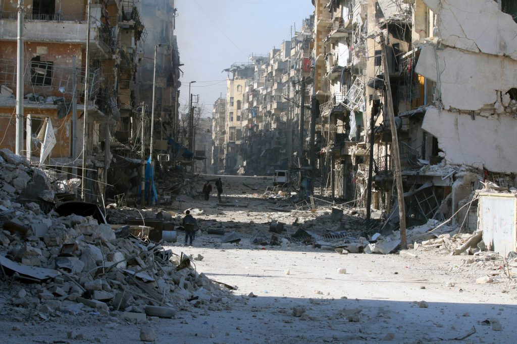 Syrians walk over rubble of damaged buildings, while carrying their belongings, as they flee clashes between government forces and rebels in Tariq al-Bab and al-Sakhour neighborhoods of eastern Aleppo towards other rebel held besieged areas of Aleppo, Syria November 28, 2016. (Reuters/Abdalrhman Ismail)