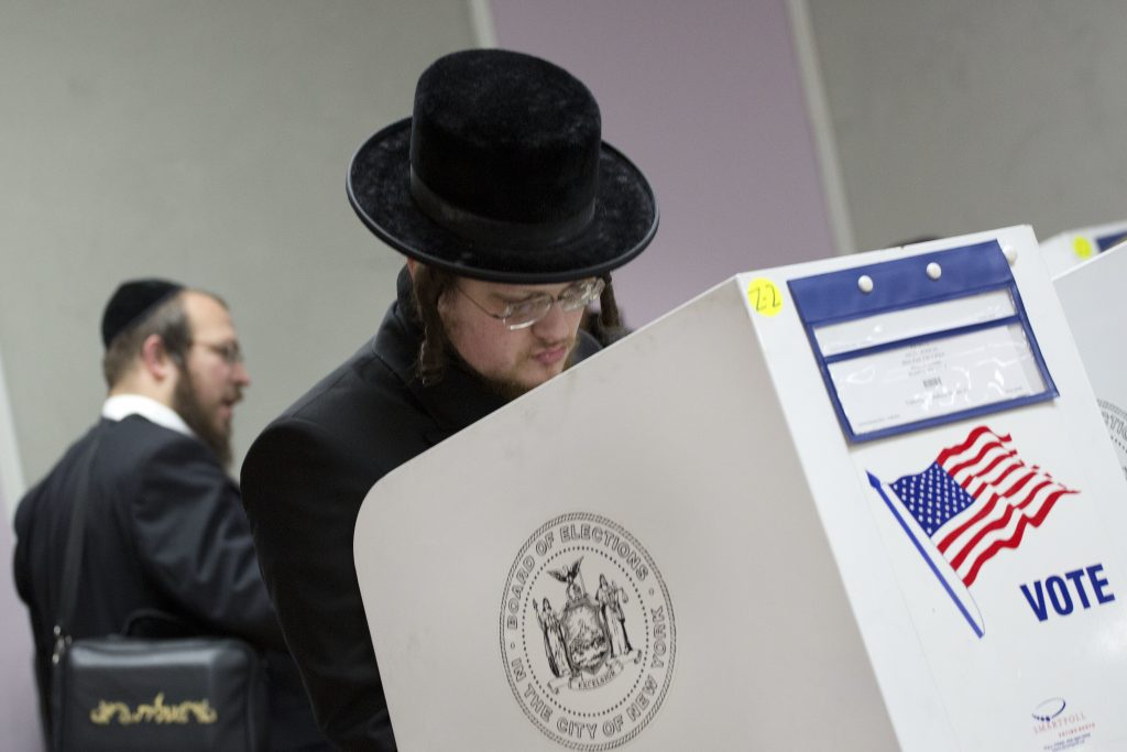 Voters mark their ballots, Tuesday, Nov. 8, 2016, in the Boro Park neighborhood in Brooklyn, New York. (AP Photo/Mark Lennihan)