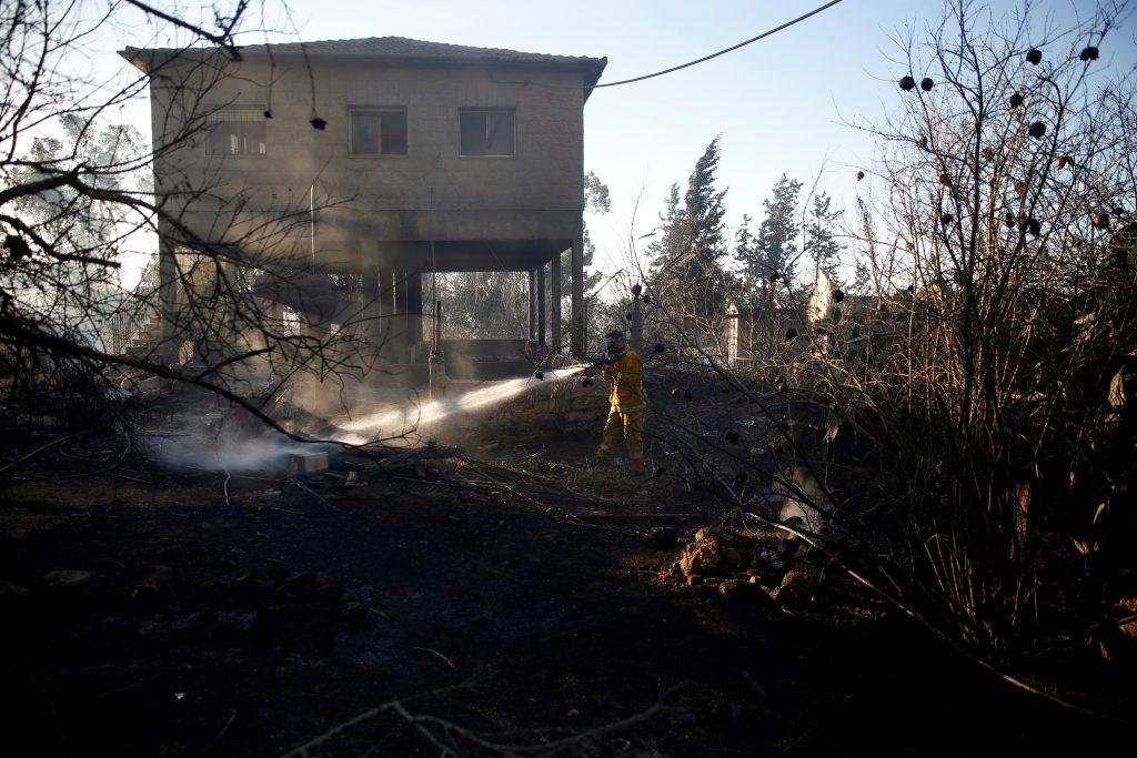 A firefighter works as a wildfire burns in the village of Beit Meir near Jerusalem November 25, 2016. REUTERS/Ronen Zvulun