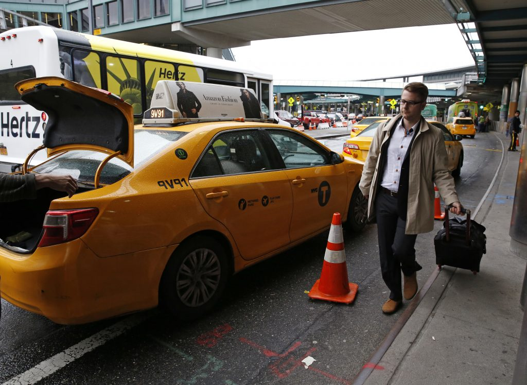 A passenger heads to a waiting taxi at LaGuardia Airport in New York. (AP Photo/Kathy Willens)