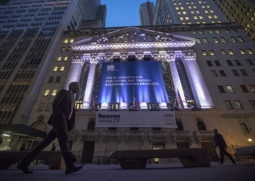 In this Tuesday, Oct. 25, 2016, photo, a pedestrian walks past the New York Stock Exchange, in lower Manhattan. Uncertainty over whether OPEC countries will back an oil production cut at their upcoming meeting, as intended, weighed on global stock markets on Monday, Nov. 28, 2016. Worries over an upcoming constitutional referendum in Italy also kept investors at bay. (AP Photo/Mary Altaffer)