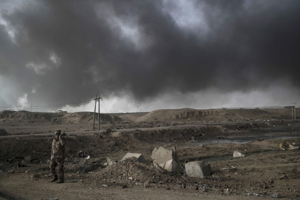A Iraqi soldier stands near a checkpoint as smoke rises from burning oil fields in Qayara, south of Mosul, Iraq, Tuesday, Nov. 1, 2016. The U.N. human rights office is lauding efforts by the U.S.-led coalition in the battle against the Islamic State group in Mosul. The office in Geneva says coalition flights over Iraq have largely succeeded in preventing IS from bringing in 25,000 more civilians to the city center, where the militant group has been using people as human shields as Iraqi forces advance on Mosul.(AP Photo/Felipe Dana)