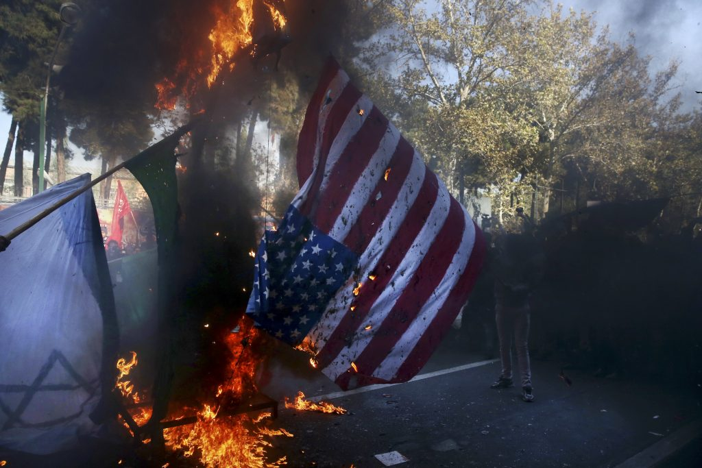 Iranian demonstrators burn representations of the U.S. and Israeli flags in a state-organized annual rally in front of the former U.S. Embassy in Tehran, Iran, on Thursday, Nov. 3, 2016, marking 37th anniversary of the seizure of the embassy by militant Iranian students. On Nov. 4, 1979, Iranian militant students stormed the U.S. Embassy, taking 52 Americans hostage for 444 days after Washington refused to hand over Iran's toppled shah, Mohammad Reza Pahlavi, for trial in Iran. The two countries have had no diplomatic relations since then. (AP Photo/Vahid Salemi)