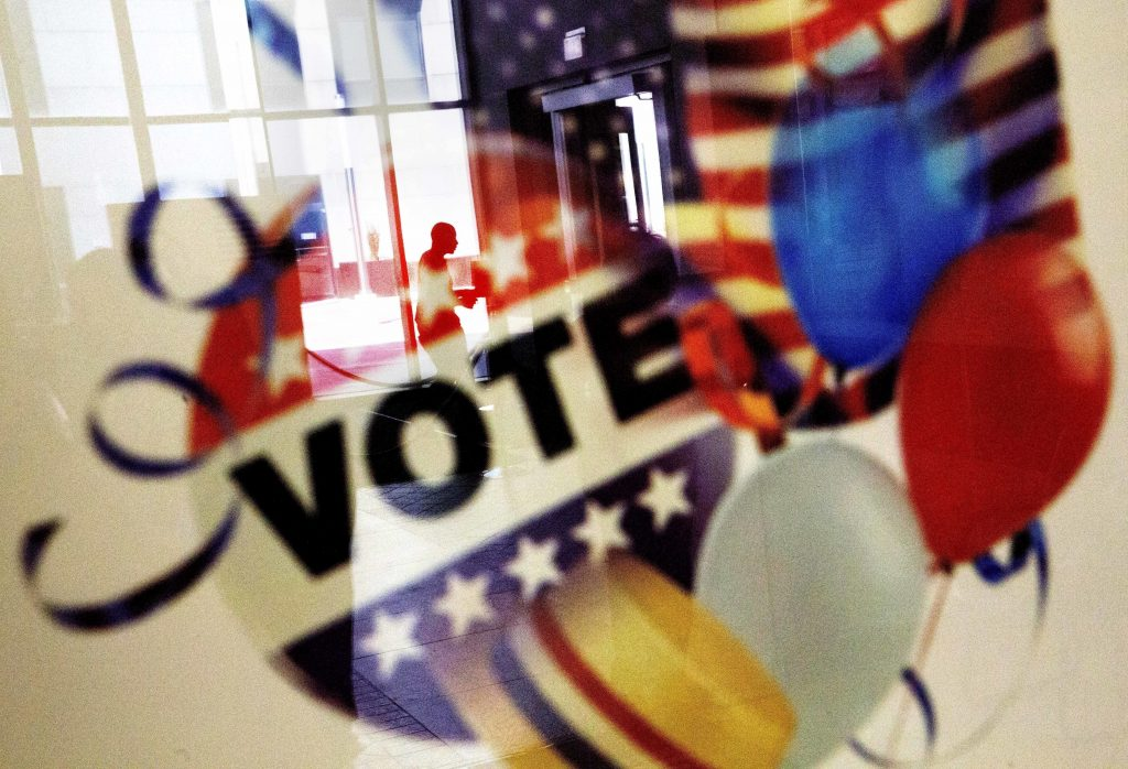 In this Nov. 1, 2016, photo, a voter is reflected in the glass frame of a poster while leaving a polling site in Atlanta, during early voting ahead of the Nov. 8 election day. (AP Photo/David Goldman)