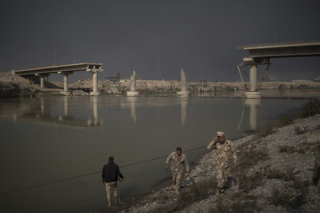 Iraqi army soldiers walk by the river near a bridge destroyed by an airstrike in Qayara, south of Mosul, Iraq, Saturday, Nov. 5, 2016. Islamic State fighters launched counterattacks in the thin strip of territory Iraqi special forces have recaptured in eastern Mosul, highlighting the challenges ahead as the battle moves into more densely populated neighborhoods where coalition air power must be used more selectively. (AP Photo/Felipe Dana)