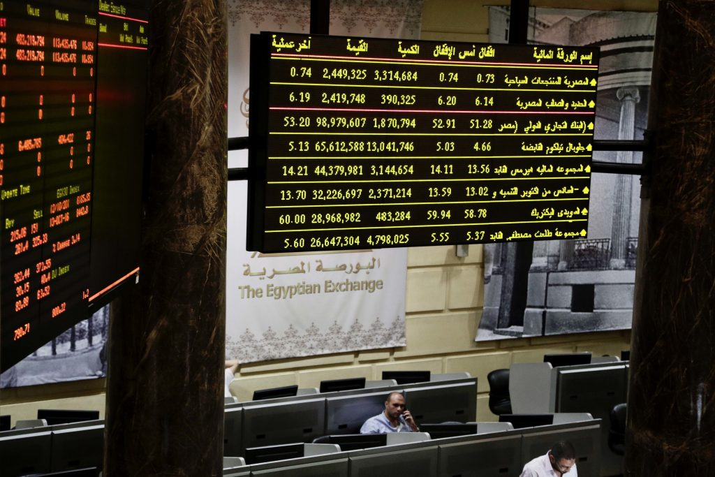 FILE - In this Thursday, Oct. 13, 2016, file photo, Egyptian traders work on the floor of the stock market in Cairo, Egypt. The Egyptian pound is trading in banks at around 16 to the dollar, down from the 13-pound peg the Central Bank set as a guiding exchange rate when it floated the currency last week. Banks were selling the U.S. currency at 16 pounds while buying it at around 15.5 pounds on Sunday, the first full business day in Egypt since the Central Bank floated the currency on Thursday. (AP Photo/Nariman El-Mofty, File)