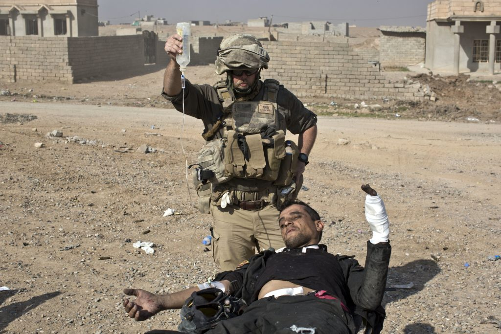 Volunteer medic Derek Coleman treats a wounded Iraqi special forces soldier at a field clinic in Gogjali, on the eastern outskirts of Mosul, Iraq, on Sunday. (AP Photo/Marko Drobnjakovic)