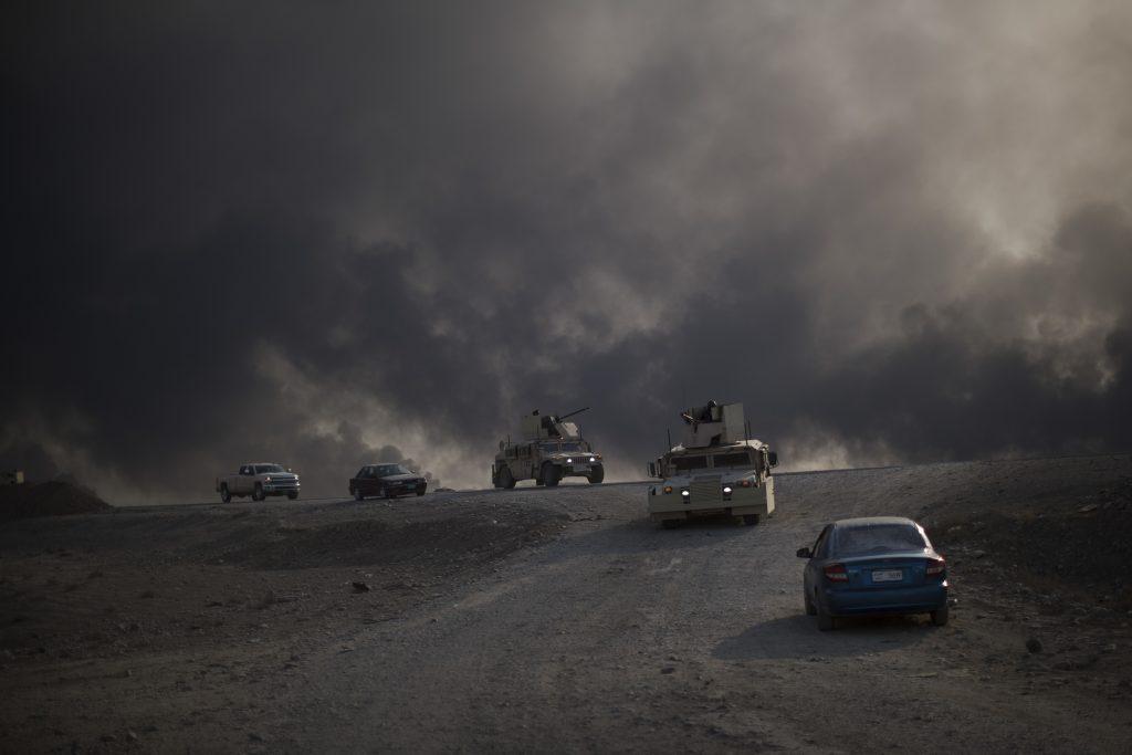 Armored vehicles move towards Hamam al-Alil from Qayara, south of Mosul, Iraq, Sunday, Nov. 6, 2016. (AP Photo/Felipe Dana)