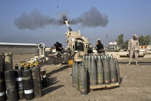 Iraqi army soldiers fire an artillery round at Islamic State positions in Bartilla, about 9 miles east of Mosul, Iraq, on Monday.  (AP Photo/Marko Drobnjakovic)