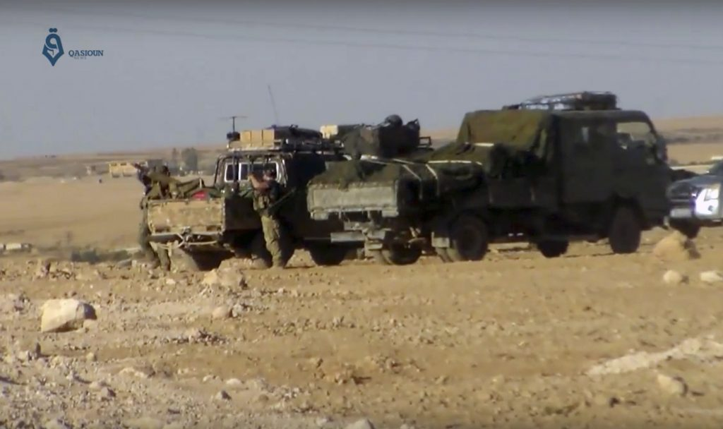 This screencap from a video provided by Qasioun, a Syrian opposition media outlet, shows U.S.-backed Syrian Democratic Forces fighters stationed near Ein Issa, north of Raqqa, Syria. (Qasioun a Syrian Opposition Media Outlet, via AP)