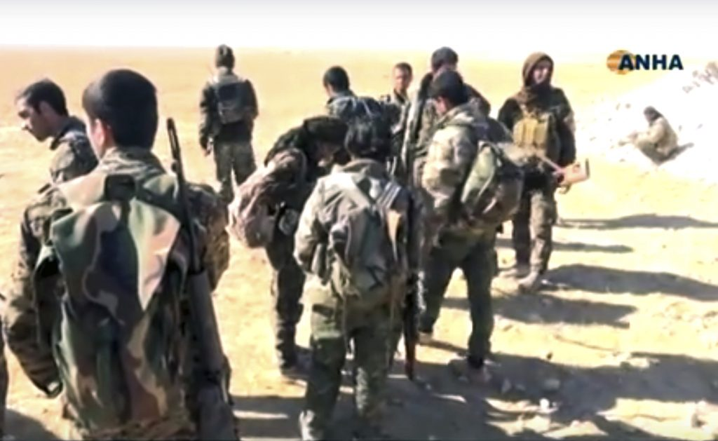 This frame grab from video provided on Monday, Nov. 7, 2016, by the Hawar News Agency, shows U.S.-backed fighters deployed during fighting with the Islamic State group in the village of Laqtah, north of Raqqa, Syria. Turkey said Tuesday that Washington has promised that U.S.-backed Syrian Kurdish forces will only be involved in encircling the Islamic State stronghold of Raqqa and will not enter the city itself. (Hawar News Agency, via AP)