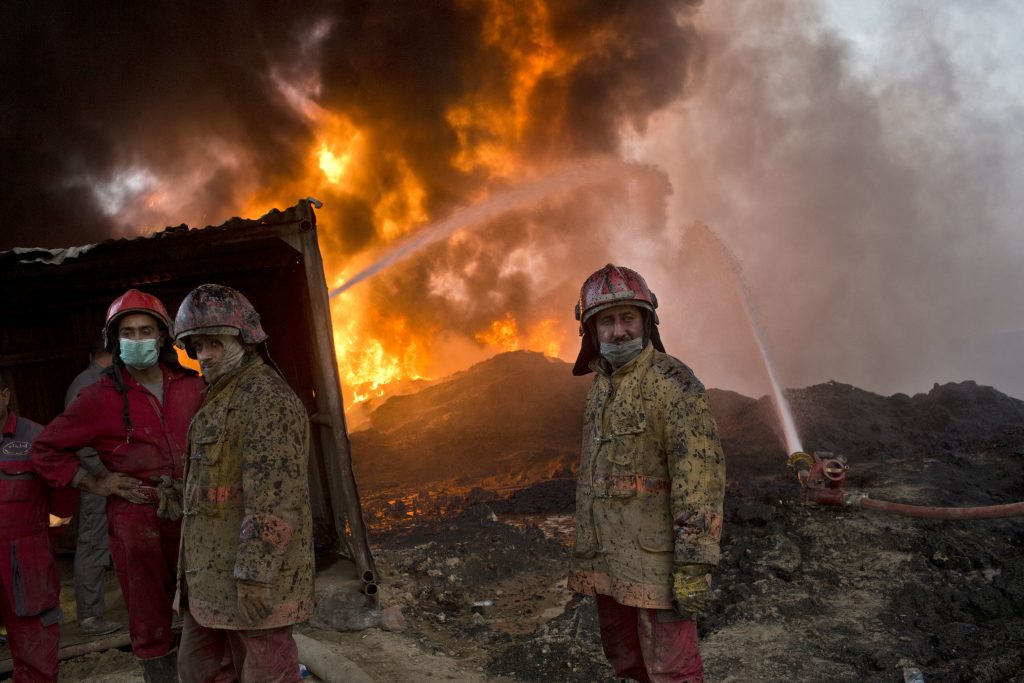 Firefighters work at the site of an oil well fire in Qayara, some 31 miles (50 km) south of Mosul, Iraq, Wednesday, Nov. 9, 2016. Iraqi firefighters worked to extinguish flaming oil wells, set alight by Islamic State militants to reduce visibility. (AP Photo/Marko Drobnjakovic)