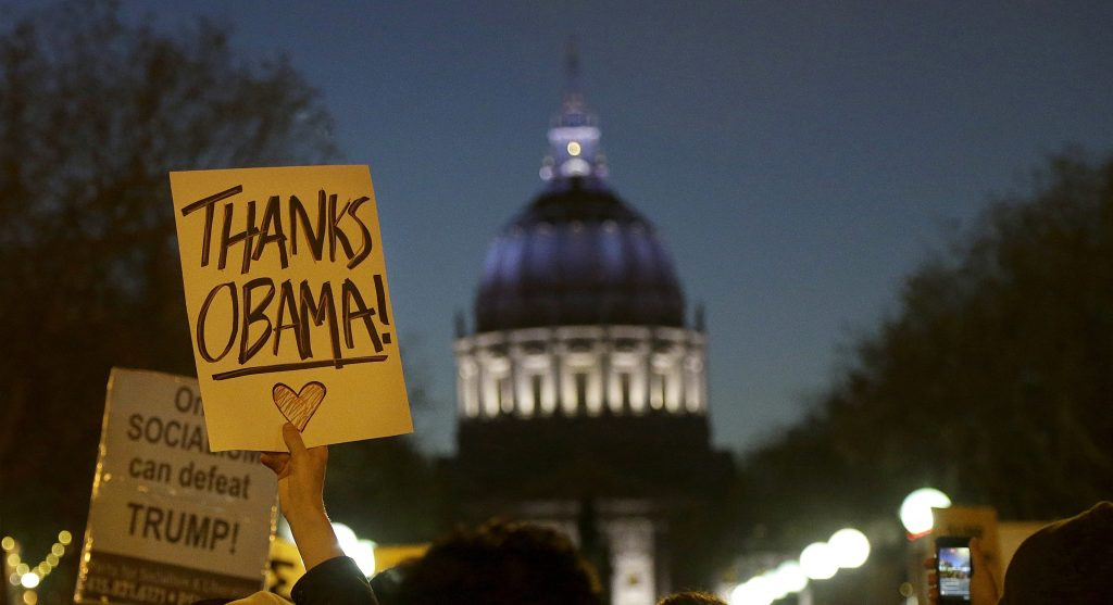 A protester holds up a sign for President Barack Obama in opposition of Donald Trump's presidential election victory in San Francisco, Wednesday, Nov. 9, 2016. (AP Photo/Jeff Chiu)