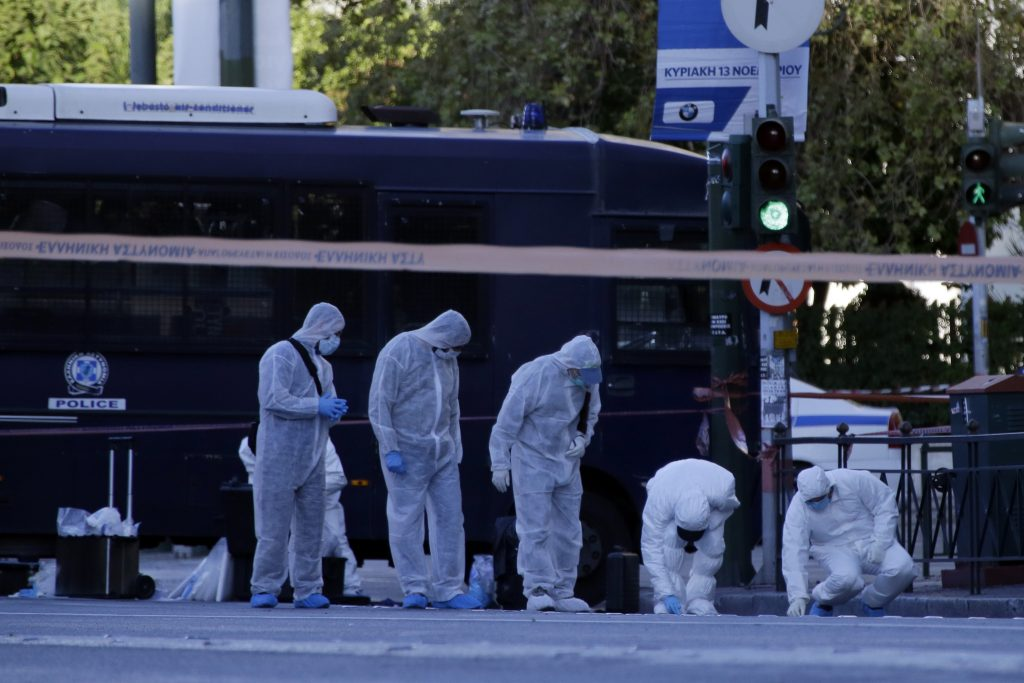 Police search for evidence after an explosion outside the French Embassy in Athens, Thursday, Nov. 10, 2016. Two unidentified individuals riding a motorcycle threw a grenade at the building and the explosion slightly injured a police officer, according to the Greek media. (AP Photo/Thanassis Stavrakis)