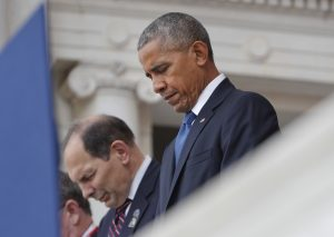 President Barack Obama and Veterans Affairs Secretary Robert McDonald bow their heads during opening prayers before the president spoke in the Memorial Amphitheater at Arlington National Cemetery during a Veterans Day ceremony on Friday. (AP Photo/Pablo Martinez Monsivais)