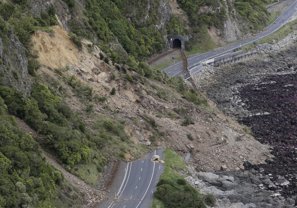 A landslide blocks State Highway One and the main railway line north of Kaikoura following an earthquake in New Zealand, Monday, Nov. 14, 2016. A powerful earthquake that rocked New Zealand on Monday triggered landslides and a small tsunami, cracked apart roads and homes and left two people dead, but largely spared the country the devastation it saw five years ago when a deadly earthquake struck the same region. (Mark Mitchell/New Zealand Herald/Pool via AP)