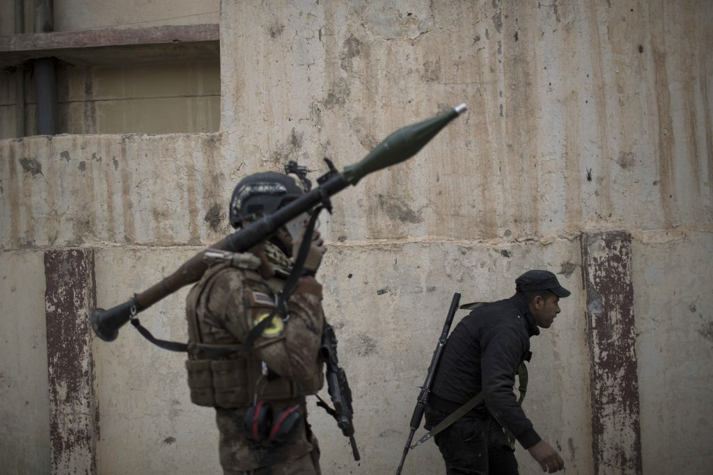 Iraqi special forces advance towards Islamic State militant-held territory in Mosul, Iraq, Wednesday, Nov. 16, 2016. Troops have established a foothold in the city's east from where they are driving northward into the Tahrir neighborhood. The families in Tahrir are leaving their homes to flee the fighting. (AP Photo/Felipe Dana)