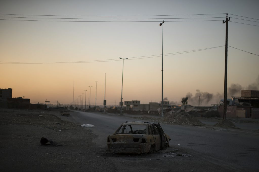 The carcass of an exploded car sits on a road as the sun sets near Mosul, Iraq, Thursday, Nov. 17, 2016. Iraqi forces launched the long-awaited operation to retake Mosul nearly a month ago but have only advanced into a few eastern districts. (AP Photo/Felipe Dana)