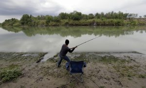 A man fishes at a ranch on the banks of the Rio Grande in Los Ebanos, Texas. The area would be cut of if a border wall is build in the area. (AP Photo/Eric Gay)