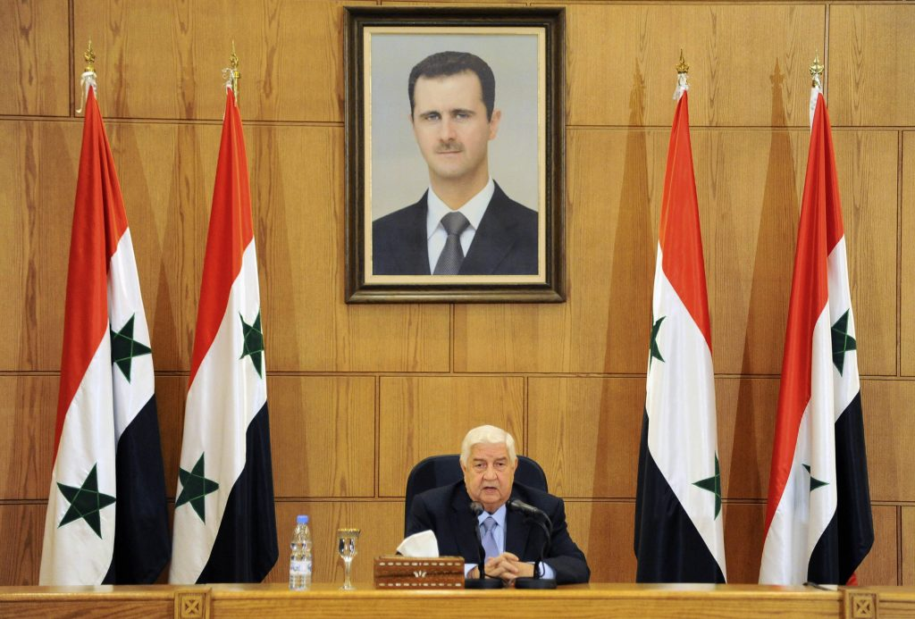 Syrian Foreign Minister Walid al-Moallem sits beneath a portrait of Syrian President Bashar Assad as he speaks during a press conference in Damascus, Syria, on Sunday. (SANA via AP)